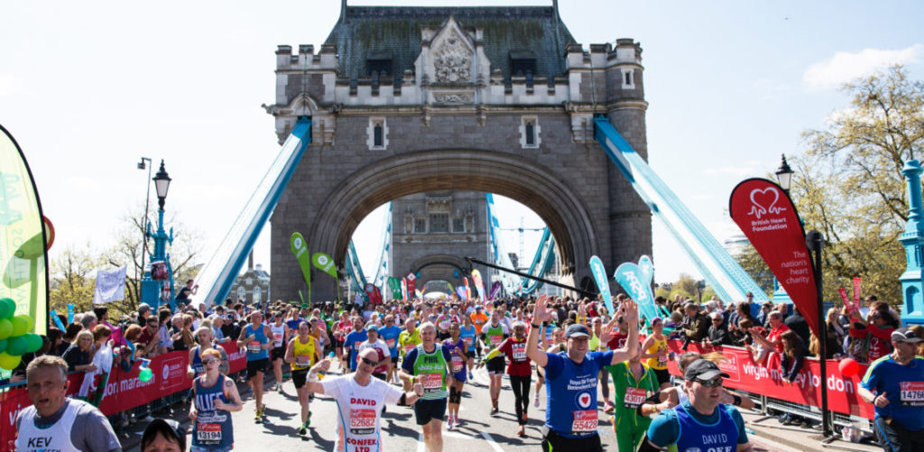 A view of runners crossing Tower Bridge, with both towers in the background.